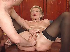 Blonde granny in black stockings fucked on table